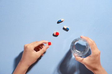 Male hand holding small pill and glass of water