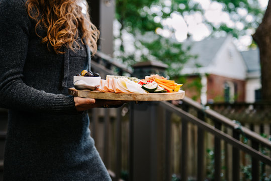 Anonymous woman carrying crudites platter