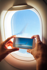 Man taking pictures with mobile phone from airplane