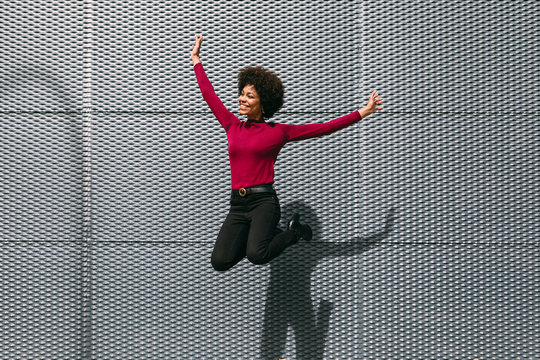 Happy black woman jumping in the street