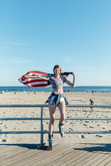 White Young Blonde Woman With Rollers Blades with US Flag Beside the Beach in Coney Island New York City . Lifestyle Stock Picture