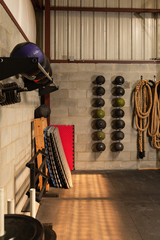 Corner of a gym with miscellaneous weights and sport equipment.