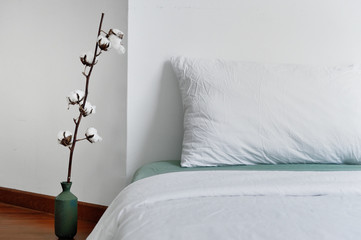 Bed with a stalk of raw cotton on the floor
