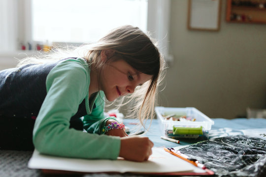 child writes letter and draws picture for dad