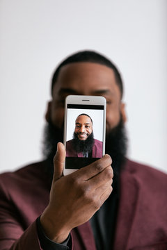 Smiling Man Holds Up Cell Phone In Front Of Face