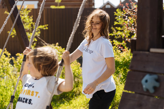 Mother pushing swing in garden