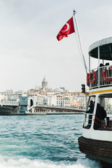 Boat with Turkish flag on water near city.