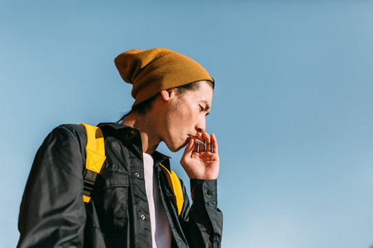 Portrait of stylish asian man smoking against a radiant blue sky