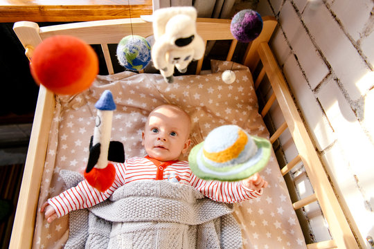 Funny baby in infant bed with mobile
