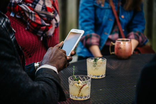 Anonymous man using smartphone during a gathering with friends