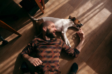 the guy is lying on the floor with the dog and laughing