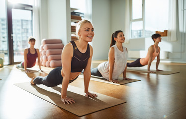 Woman smiling while doing the cobra pose in yoga class