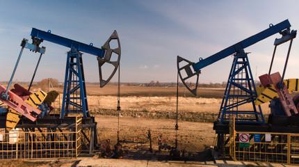 Oil pumpjacks over wells in evening