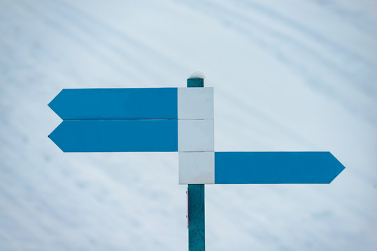 Blank direction signs in a ski resort to indicate ski runs.
