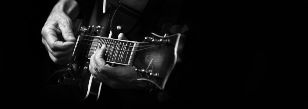 Guitarist hands and guitar close up. playing electric guitar.  black and white. copy spaces