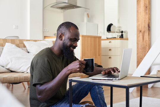 Black afro male working from home having coffee.
