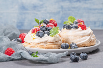 Mini pavlova meringue cakes with fresh raspberries and blueberries with mint leaves.