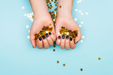 Hands with black manicure holding golden stars. Flat lay style.