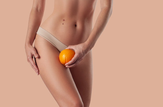 Slim woman is holding orange. Perfect female hips in underwear w