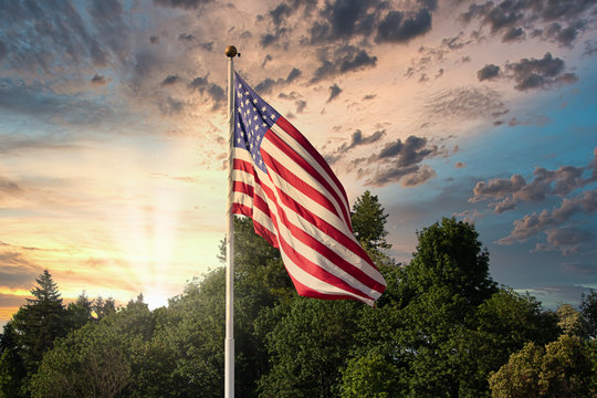 sunset and weather with cloudy sky behind american flag blowing in the wind