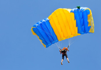 Skydiver under yellow and blue parachute dome