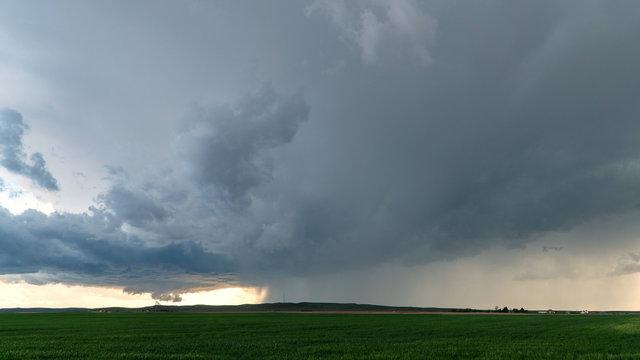 Tornado touching ground behind rainstorm in Nebraska in wide view of severe storm.