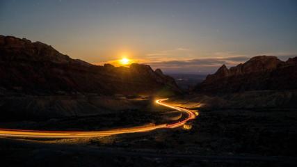 Traffic driving on winding road through the desert in Utah on I-70 as the moon rises. Fotomurales