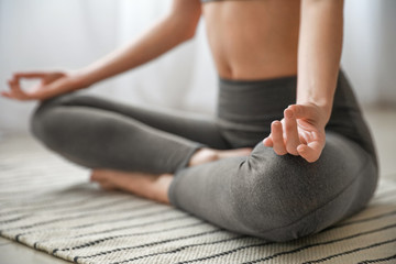 Beautiful young woman practicing yoga at home, closeup