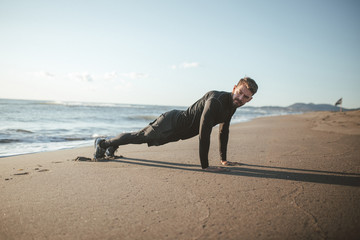 Young bearded men doing push ups at the beach wearing black sport clothes