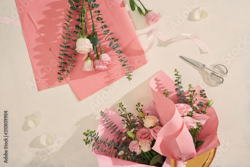 Making pink flowers bouquets with scissor on white background. Holiday, mothers day, valentine day concept. Top view, flatlay