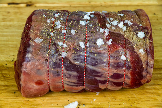 Rolled beef brisket on a wooden chopping board seasoned with sea salt flakes and pepper.