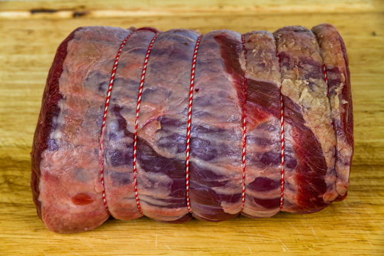 Rolled beef brisket on a wooden chopping board.