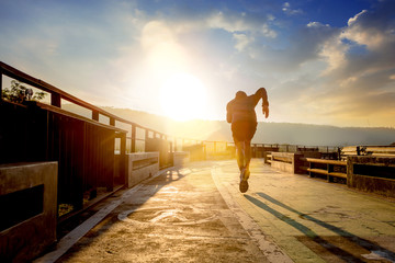 Silhouette of man running sprinting on walk way. Fit male fitness runner during outdoor workout with sunset background. Fotomurales