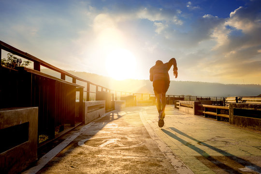 Silhouette of man running sprinting on walk way. Fit male fitness runner during outdoor workout with sunset background.
