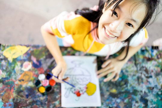 Top view,happy asian female people enjoy paint activities having fun,relax, smiling teenage girl with palette and paintbrush to painting watercolor on canvas, art,creativity,development of children