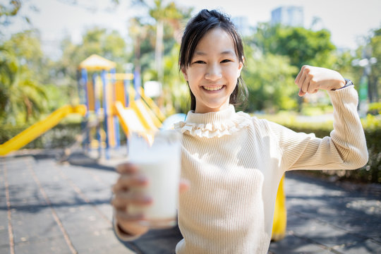 Asian child girl holding a glass of milk,showing her bicep to tell she is strong,healthy female teenage drink fresh milk,looking at camera and smiling in outdoor at park on the playground,health care