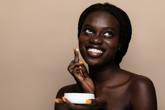 Young african american beauty using face cream isolated on beige background