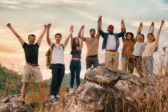 group of diversity people having fun together climbing up rocky mountains to the peak