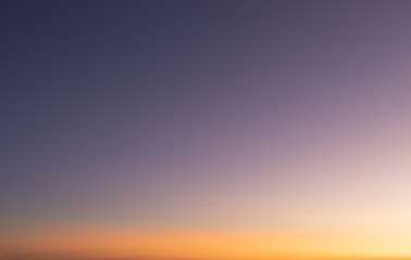 Heaven at early morning with copy space. Smooth orange blue gradient of dawn sky.Sunset, sunrise backdrop.Predawn clear sky with orange horizon and blue atmosphere. Background of beginning of day.