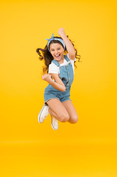 Active girl feel freedom. Fun and relax. feeling free. carefree kid on summer holiday. time for fun. retro beauty in mid air. Jump of happiness. small girl jump yellow background. full of energy.