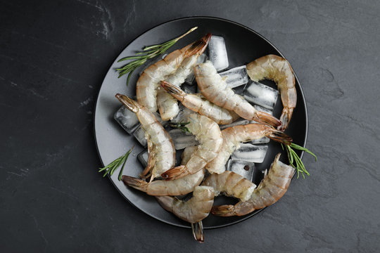 Fresh raw shrimps with rosemary and ice cubes on black table, top view