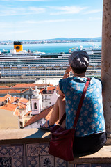 View of Lisbon from Alfama district with a tourist (Portugal)