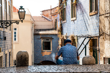 Reading tourist in Alfama district, Lisbon, Portugal