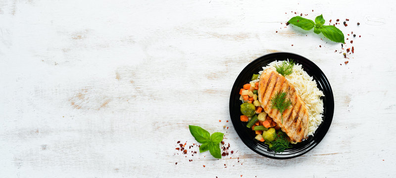 Baked chicken fillet with rice and vegetables on a black plate. Top view. Free copy space.