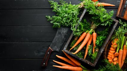 Fototapeta Fresh carrots on a black wooden background. Top view. obraz