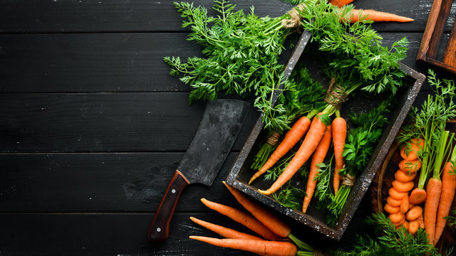 Fresh carrots on a black wooden background. Top view.
