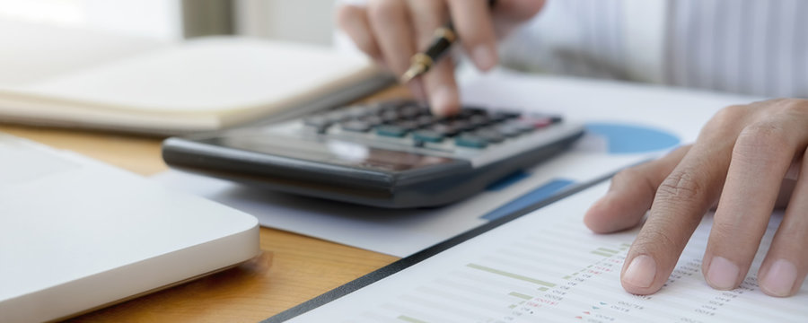 Close-up of businessman hand using calculator to calculate business data, accountancy document at home office.