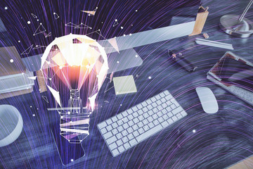 Computer on desktop in office with bulb icon hologram. Multi exposure. Concept of idea.