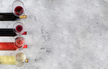Spoed Foto op Canvas Wijn Different Wine bottle and Wine glasses with bordeaux, red, rose and white on concrete background. Top view. Abstract wine wallpaper.