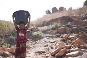 Foto auf Leinwand Cappuccino Landscape shot of African Black Schoolgirl Walking with Heavy Water Bucket